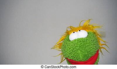 Funny green puppet talking like an actor in camera