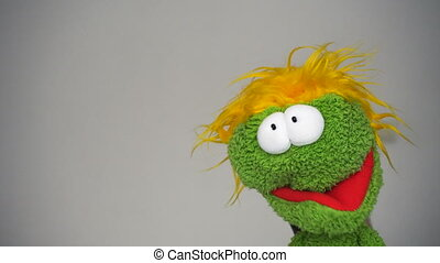 Funny green puppet with funny face looking in camera