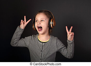 Funny grimacing kid girl listening the music, singing in wireless headphones and showing the hands v sign on grey dark background