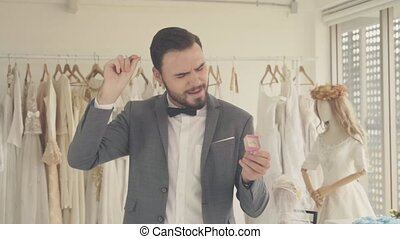 Funny groom dance in dressing room with happiness while wearing a wedding costume suit before the engagement or wedding ceremony.