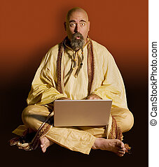 Funny Guru looks up over the top of his laptop computer.