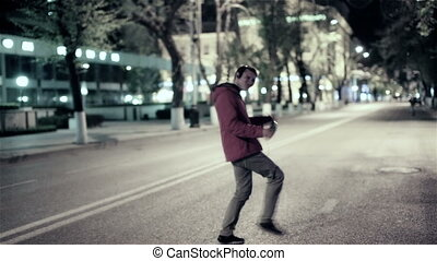 Funny guy walking down the street the night city, freely dancing to music in headphones.