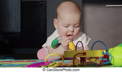 Funny happy baby girl crawls with toy teething on stomach and sways on knees in bright sunlight nursery