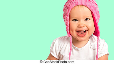 Funny happy baby girl in a pink  winter knitted hat laughing