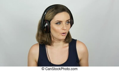 Funny happy beautiful girl with big headphones on her head is listening to music and dancing. Portrait of a girl on a white background in studio