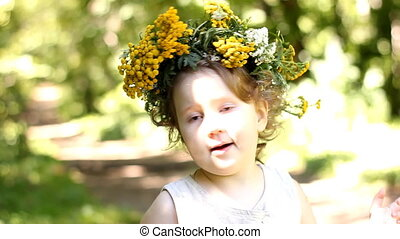 Funny happy child with a wreath from a wild flower on his head.