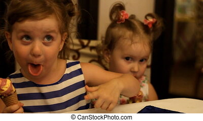 Funny happy children eat dessert and ice cream at a party, laugh, rejoice. The child laughs and depicts the clown, the emotions of humor.