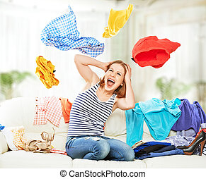 Funny happy girl with flying clothes on the sofa at home