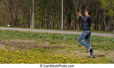 Funny happy man run through the meadow with a flower
