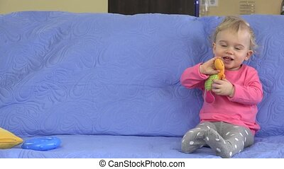 Funny happy toddler girl playing with her toys on sofa.