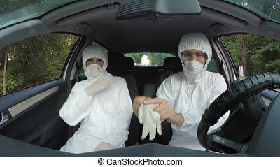 Funny hazmat scientist workers in car dancing and putting on...