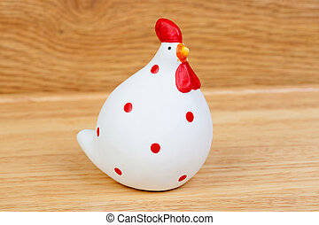 Funny hen ceramic white and red on a wooden background