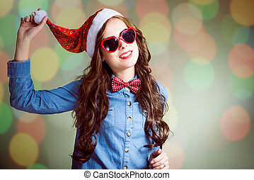 Funny hipster girl in heart shaped sunglasses and Santa hat