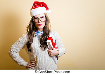 Funny hipster girl in santa hat carrying a present box