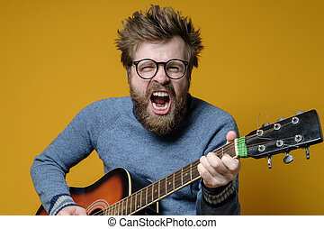 Funny hipster in an old sweater plays an acoustic guitar and...