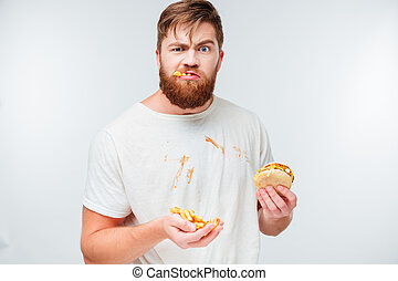Funny hungry bearded man eating junk food isolated on white...