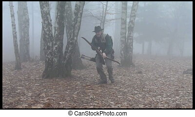 funny hunter - bow hunter in the foggy forest