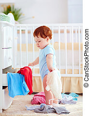 funny infant baby throwing out clothes from the dresser at...
