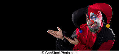 funny Jester showing to copyspace, concept halloween and horror, black background