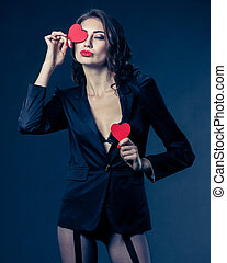 Funny Joyful Girl with Valentine Heart? over her Eyes. Laughing Young Woman in love. on black background