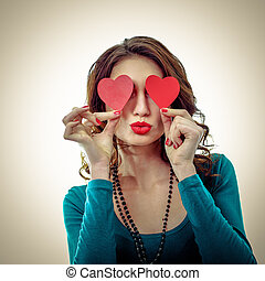 Funny Joyful Girl with Valentine Hearts over her Eyes. Laughing Young Woman in love. Isolated on a White Background