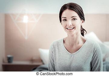 Funny joyful woman sitting and smiling.