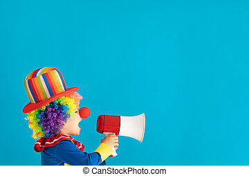 Funny kid clown shouting by megaphone