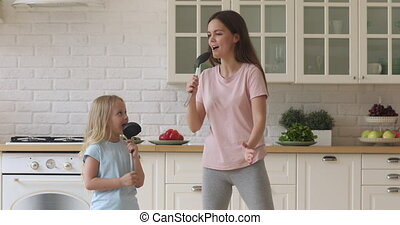 Funny kid daughter and mom singing in kitchenware in kitchen