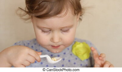 Funny kid eats food with a spoon.