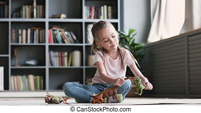 Funny cute small kid girl having fun playing dinosaurs alone sitting on carpet, adorable preschool pretty child having fun holding dino toys enjoying leisure playtime imagine activity game at home