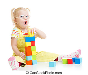 Funny kid in eyeglases making tower using blocks with letters isolated