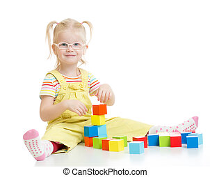 Funny kid in eyeglases playing building blocks isolated