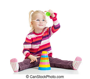 Funny kid in glasses playing colorful pyramid toy isolated