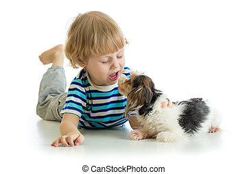 Funny kid little boy kissing puppy dog. Isolated on white background.