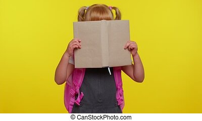 Funny positive kid primary school girl with ponytails wearing uniform peeping while hiding behind a book playfully posing on yellow background. Child student with book portrait. Back to school concept