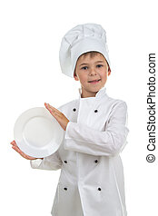 Funny kid wearing chef uniform holding plate in his hands on white background.