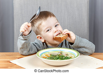 Funny kid with piece of bread and plate of soup