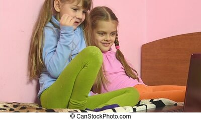 Funny kids sitting on the bed looking at the laptop screen
