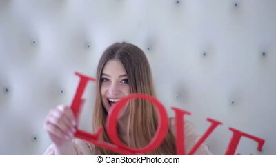Funny lady showing sign with word love.