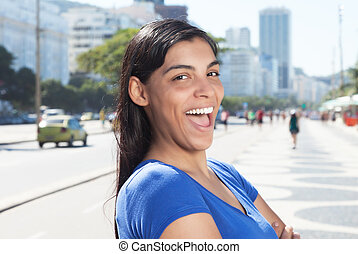 Funny latin woman with long dark hair in the city