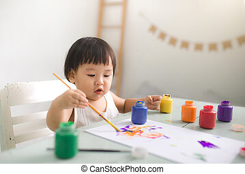 Funny laughing asian baby girl drawing with colorful pencils at home