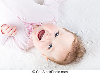 Funny laughing baby girl on a white knitted blanket