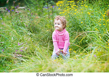 Funny laughing baby girl playing in a blooming garden