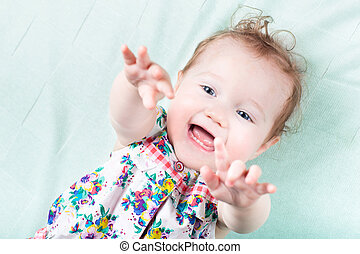 Funny laughing baby girl playing on a green blanket
