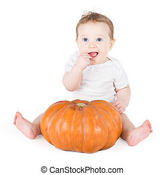 Funny laughing baby girl playing with a huge pumpkin on white ba