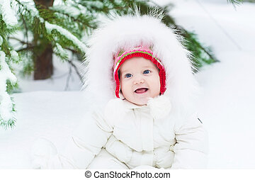 Funny laughing baby girl sitting in snow under a Christmas tree