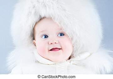 Funny laughing baby in a big white fur hat