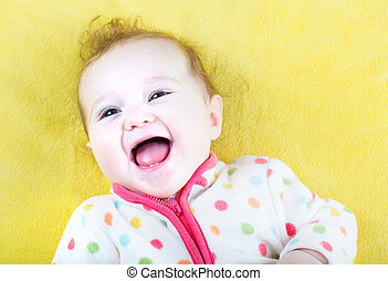 Funny laughing baby in a colorful sweater on yellow blanket