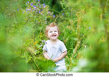 Funny laughing baby in a green summer field