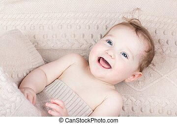 Funny laughing baby under a knitted blanket